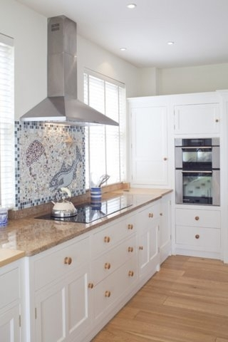 Wooden venetian blinds complete this stylish kitchen with its seaside mosaic tiles above the hob