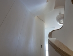 New staircase and curved joinery units following curvatures of original stair case above.